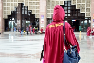 Pengunjung wanita yang tidak berjilbab diwajibkan memakai jubah